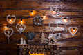 Bulbs garland lights at the wooden boards wall above fireplace