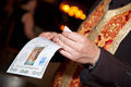 A bulgarian priest holding certificate of orthodox baptising ceremony close up s hands in church baptismal Stock Photos