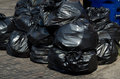 Bulging black bags of trash and rubbish sit alongside a curb for trash pick up Royalty Free Stock Photo