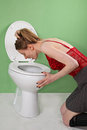 Bulimic girl young skinny vomiting over toilet Royalty Free Stock Photos