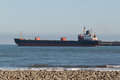 Bulk carrier ship an image of a passing close to a beach Stock Images