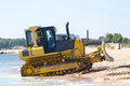 Bulldozer on the beach shoveling sand Royalty Free Stock Image
