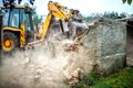 Bulldozer demolishing concrete brick walls of small building Royalty Free Stock Photo