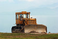 Bulldozer a lone with sea in the background Stock Photography