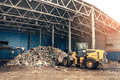 The bulldozer will clean the waste dump. Waste processing plant. Technological process. Business for sorting and