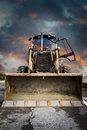 Bulldozer, Yellow tractor on dramatic sky background Royalty Free Stock Images