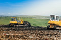 bulldozers working on construction site. Details of wasteland, garbage disposal dumping grounds Royalty Free Stock Photo
