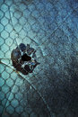 Bullet hole in window a cracked and broken blue tinted with what looks like a Stock Images