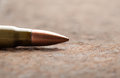 Bullet on rusted metal background macro of kalashnikov iron Royalty Free Stock Photography