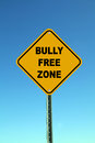 Bully free zone yellow school road sign against a beautiful blue sky Royalty Free Stock Image
