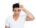 Bully man closeup portrait of funny mad young displaying loser sign on his forehead and looking at you with disgust isolated on Stock Photography
