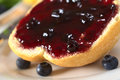 Bun with blueberry jam on half a some fresh blueberries around selective focus focus on the front of the and Royalty Free Stock Images