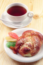 Bun and cup of tea sweet with dried fruit on wooden table Stock Images