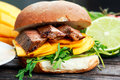 Bun with grilled roast beef, mango and arugula. Royalty Free Stock Photo