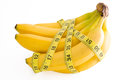 Bunch of bananas a isolated on a white background with measuring tape around them showing diet concept Royalty Free Stock Image