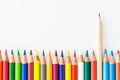 Bunch of colorful pencils with one graphite pencil standing out Royalty Free Stock Photo