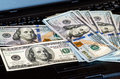 Bunch of dollar bills thrown on a laptop keyboard featured defocused bokeh pack one hundred dollars notes Stock Images