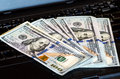 Bunch of dollar bills thrown on a laptop keyboard featured defocused bokeh pack one hundred dollars notes Stock Image