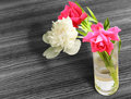 Bunch of flowers in a glass with water on table Stock Images
