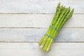 Bunch of fresh asparagus on a white wooden table. Royalty Free Stock Photo