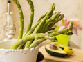 A bunch of fresh green asparagus with avocado and bottle in background Stock Photos