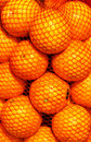 Bunch of fresh orange fruits in a string bag on market fruit background Royalty Free Stock Photography