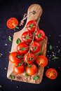 A bunch of fresh organic cherry tomatoes with sea salt and basil in olive cutting board Royalty Free Stock Photo