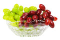 Bunch of grapes green and red juicy lying in a glass vase isolated on white background Royalty Free Stock Photo