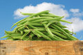 Bunch of green beans in a wooden crate against a blue sky with clouds Stock Photos