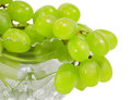 Bunch of green grapes hanging from the edges the transparent vase on white background Stock Images
