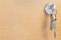 Bunch of home keys in lock of wooden door Royalty Free Stock Photo