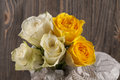 Bunch of multicolor rose flowers wrapped in newspaper over brown Royalty Free Stock Photo