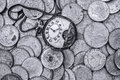 A bunch of old silver coins with a broken pocket watch on top Royalty Free Stock Photo