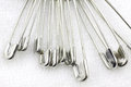 Bunch of safety pins on fabric Royalty Free Stock Photo