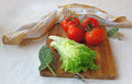 Bunch of tomato and a head of lettuce on the board clary sage leaves kitchen table Royalty Free Stock Images