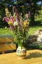 Bunch of wildflowers outdoors in vase ceramic filled with assorted on a wooden table on a sunny day Stock Photo