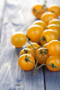 Bunch of yellow cherry tomatoes on wooden table Royalty Free Stock Photo