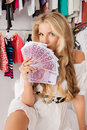 Bundle of money fashionable girl sitting with a in a store shopping Royalty Free Stock Image