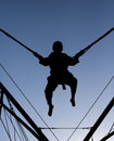 Bungee jump silhouette a black of a boy jumping and being suspended in mid air by cords Stock Photo