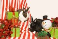 Bunnies and christmas gifts two rabbits sit with a toy snowman among holly poinsettias Stock Photography