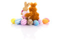 Bunnies hug easter eggs over white background Royalty Free Stock Photography
