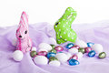 Bunnies and their egss image of chocolate in colorful wrapping with different sized colored chocolate eggs all placed on purple Royalty Free Stock Photography