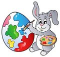 Bunny artist painting Easter egg Stock Photos
