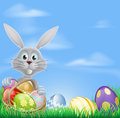 Bunny and chocolate easter eggs the with a basket of a grass field background Stock Photography