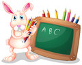 A bunny with coloring pens beside a blackboard Royalty Free Stock Photo