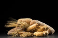 Buns, baguette, ciabatta and bread on dark wooden table. Rye, barley, wheat, oats and many fresh mixed breads  on black ba Royalty Free Stock Photo