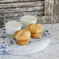 Buns and glasses of milk on a  rustic wood background. Royalty Free Stock Photo