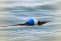 Buoy floating on surface of calm lake waters boundary in swimming area of beach Royalty Free Stock Photo