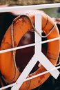Buoy or lifebuoy ring on shipboard in evening sea. Flotation device on ship side on seascape. Safety, rescue, life