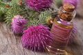 Burdock oil in a glass bottle on a background of flowers macro horizontal Stock Photo